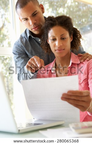 Worried Young Couple Using Laptop At Home