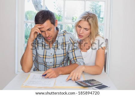 Worried young couple with financial documents and calculator sitting at home - stock photo