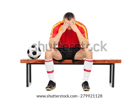 Worried young football player sitting on a wooden bench with his head down isolated on white background - stock photo