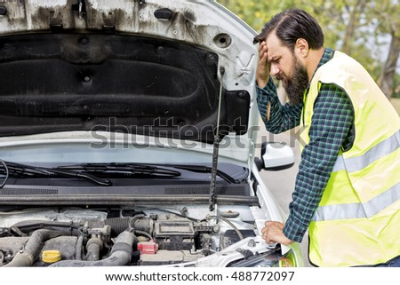 Worried young man examining his car engine parked on the side of a road