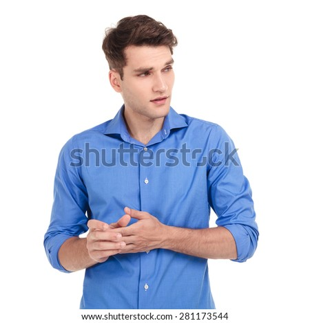 Worried young man holding his hands together while looking to his side. - stock photo
