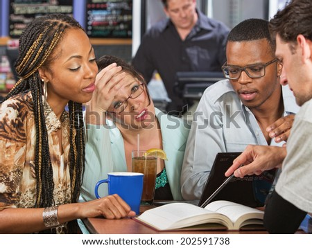 Worried young student with friends studying in cafe - stock photo