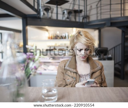 Worried young woman reading text message on cell phone in cafe - stock photo