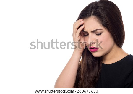 Worried young woman touching her forehead - stock photo