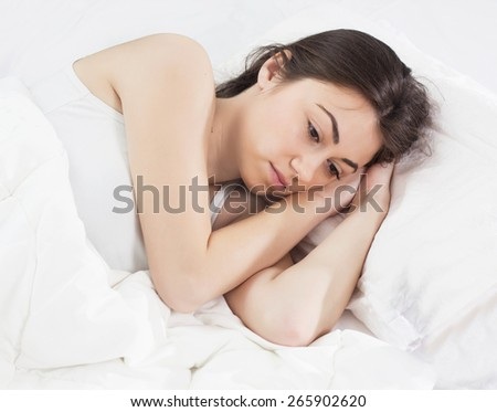 Worried Young Woman with Insomna laying in the bed. - stock photo