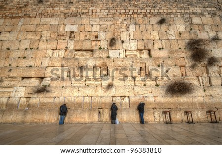 Worshipers at the Western  Wall in Jerusalem, Israel. The wall is one of the holiest sites in Judaism except for the Temple Mount itself. - stock photo