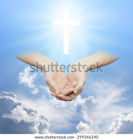 Worshiping the Divine Source of Love and Light - female hands cupped with a shining white cross hovering above on a sunny blue daytime sky with fluffy clouds - stock photo