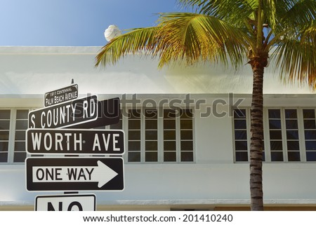 Worth Avenue street sign with palm tree and art deco style architecture at Palm Beach, Florida, United States - stock photo