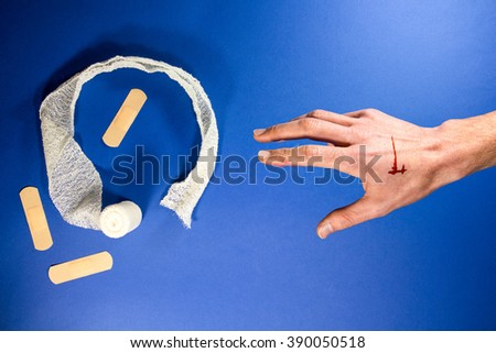Wounded arm reach for white bandage and plaster on a blue health background - stock photo