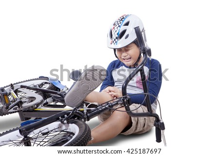 Wounded child falling from his bike and crying while holding his knee, isolated on white background