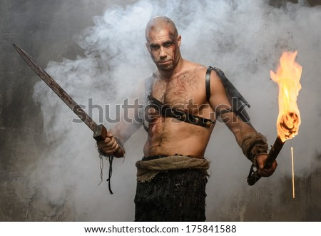 Wounded gladiator holding torch and sword covered in blood  - stock photo