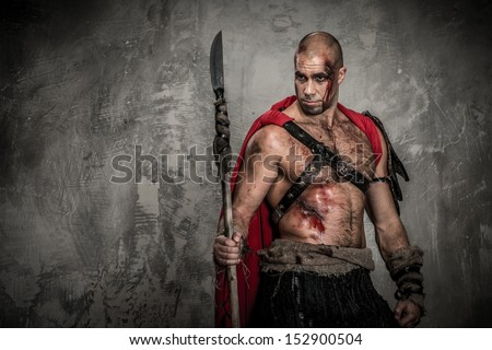 Wounded gladiator in red coat with spear - stock photo