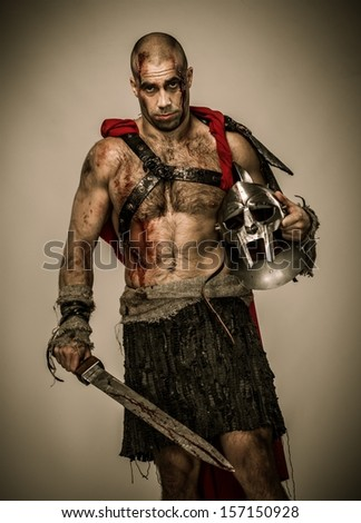Wounded gladiator with sword covered in blood and helmet isolated - stock photo