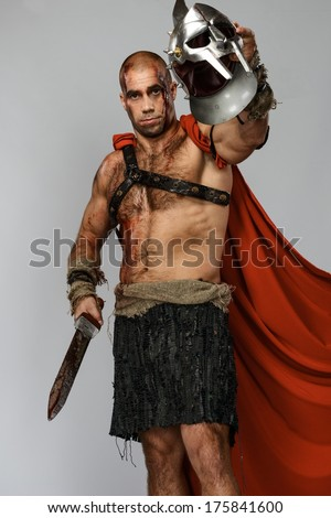 Wounded gladiator with sword covered in blood and helmet isolated on grey
