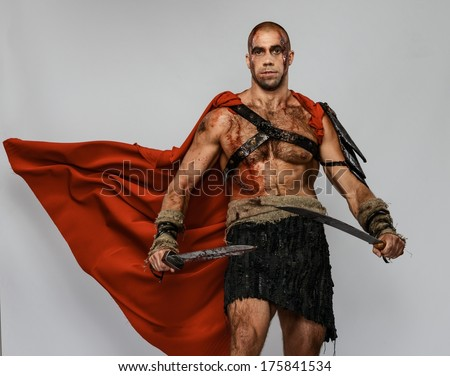 Wounded gladiator with two swords covered in blood isolated on grey - stock photo