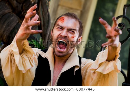 Wounded male vampire raising his arms and screaming