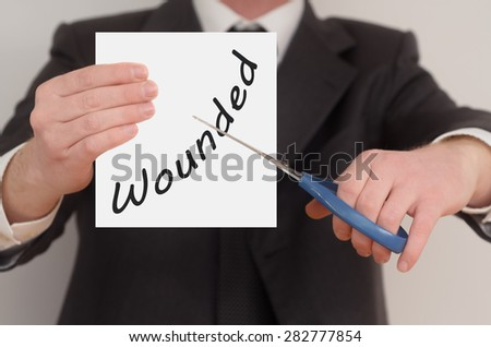 Wounded, man in suit cutting text on paper with scissors