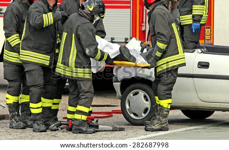 wounded person carried by firefighters on a stretcher after the road accident - stock photo