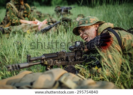 Wounded soldier shoots lying on the grass - stock photo