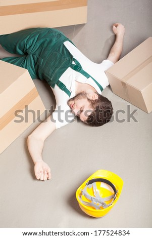 Wounded warehouse worker lying unconscious on the floor after accident  - stock photo