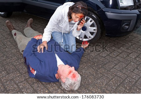 Wounded woman calling for an ambulance after a car accident - stock photo
