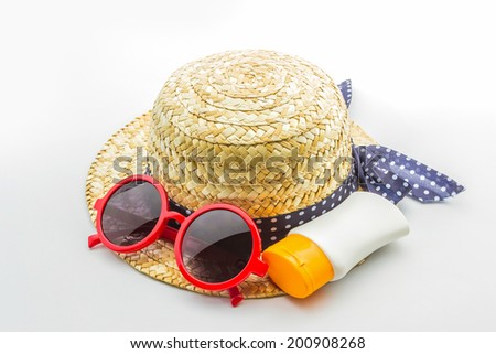 Woven hat, red sunglasses with body lotion on white background. - stock photo