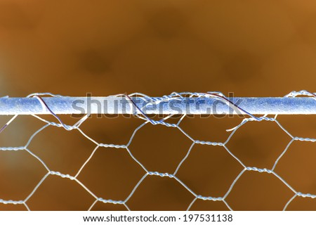 Woven rusty wire fence - texture with inverted colors - stock photo