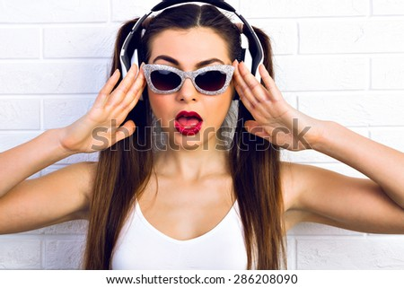 Wow! Excited young woman surprised looking at the camera wearing sunglasses, headphones, listening to music on a white background. Surprised emotions. ready for party.