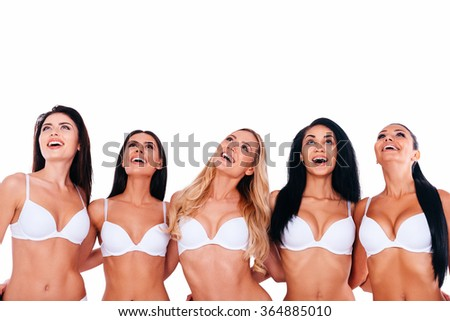 Wow! Group of beautiful young women in lingerie embracing and looking up with smiles while standing against white background - stock photo