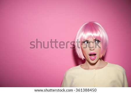 Wow. Portrait of cheerful young woman in pink wig staring at something with shock. Her mouth and eyes are wide open. Isolated and copy space in left side - stock photo
