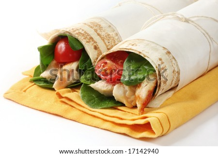 Wrap sandwiches filled with grilled chicken, spinach leaves, and cherry tomatoes.  Flat bread tied with paper and string.