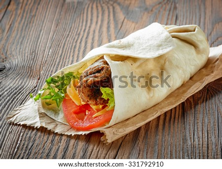 wrap with beef and vegetables on wooden table - stock photo