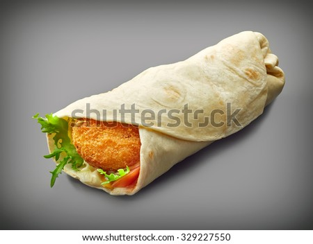 Wrap with fried chicken and vegetables on a dark gray background