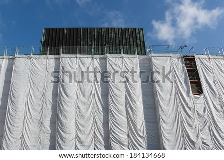 Wrapped building at construction site, scaffolding and wrinkled canvas