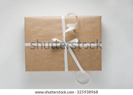 Wrapped gift box on white wooden background, top view. Filter effect - stock photo