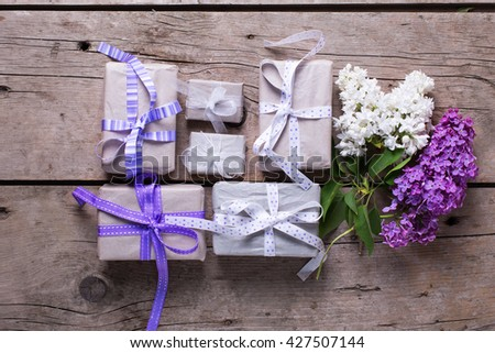 Wrapped  gift boxes with presents  and lilac flowers on vintage wooden background. Selective focus. Place for text. Flat lay. - stock photo