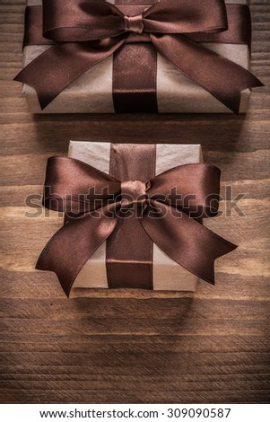 Wrapped gift containers with brown ribbons on vintage wooden board.