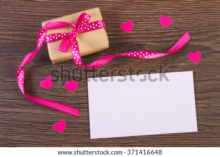 Wrapped gift with ribbon and love letter in envelope on wooden background, decoration for Valentines Day, copy space for text - stock photo