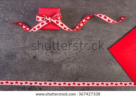 Wrapped gift with ribbon and love letter in red envelope on structure of concrete, decoration for Valentines Day, copy space for text - stock photo