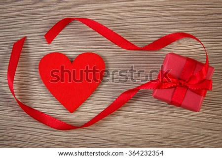 Wrapped gift with ribbon and valentine red heart on wooden background, decoration for Valentines Day, symbol of love, copy space for text - stock photo