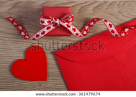 Wrapped gift with ribbon, red wooden heart and love letter in envelope on wooden background, decoration for Valentines Day, copy space for text - stock photo
