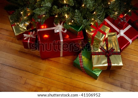 Wrapped gifts under a Christmas tree with room for copy - stock photo
