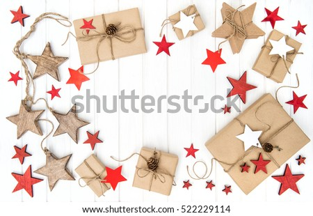 Wrapped gifts with christmas decoration red stars on bright wooden background. Flat lay.