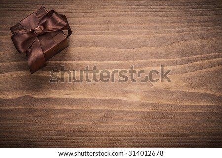 Wrapped glittery gift container on vintage wooden board copyspace.