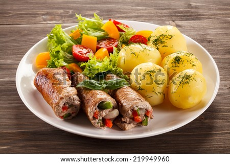 Wrapped pork chops, boiled potatoes and vegetables - stock photo