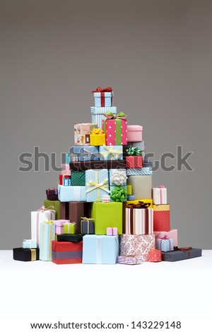 Wrapped presents stacked in the form of a pyramid with cute Gift boxe at the top.  Group of presents. Gift boxes with origami bows.  - stock photo
