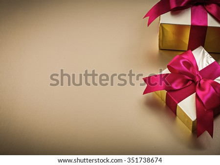 Wrapped presents with tied bows on golden surface holidays concept. - stock photo