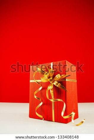 Wrapped red present box against red background