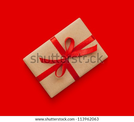 Wrapped vintage gift box with red ribbon bow, isolated on red
