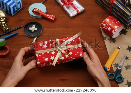 Wrapping christmas gift (also available as footage) - stock photo